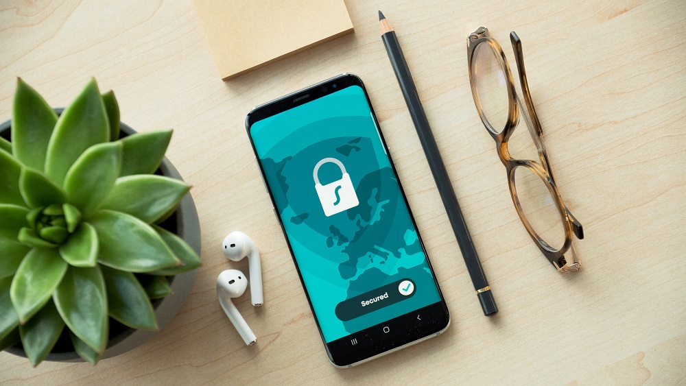 "Mobile phone on desk with ""secured"" image of padlock, cybersecurity concept"
